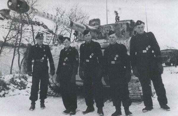 전설적인 전차 에이스 미하일 비트만(맨 왼쪽)이 같은 차량 전차병들과 찍은 사진. 비트만의 사진 중 가장 잘 알려진 사진이다. 1944년 1월 14일, 뛰어난 전공으로 기사철십자훈장(Knight's Cross of the Iron Cross)을 수여받은 뒤 찍은 것이다. 뒤에 보이는 전차는 독일군의 티거 I 중전차(E형)다.