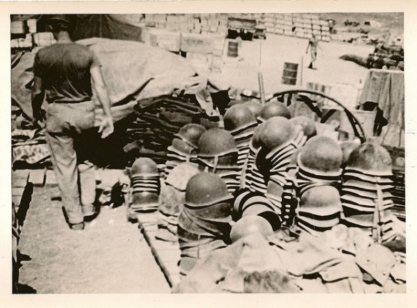 한 미군 해병대원이 차곡차곡 정리된 철모들을 지나고 있다. 1945년 2월, 일본 남부 이오지마.