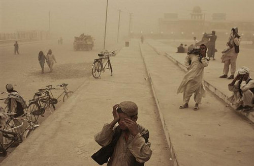 A boy covers his eyes during a sandstorm in the southern city of Kandahar ⓒ Moises Saman