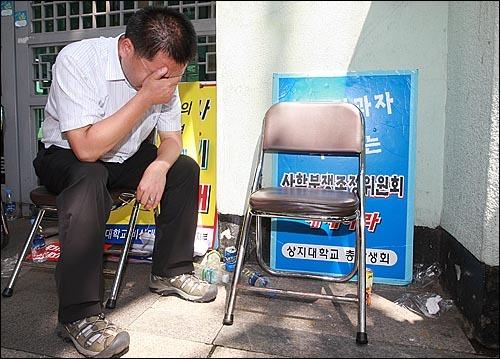 교육부 앞에서 비리재단 복귀 상경투쟁을 벌이던 상지대 학생들이 연행되자 고개를 떨구고 눈물을 흘리는 진관장  노조지부장. (2010년 8월 9일)